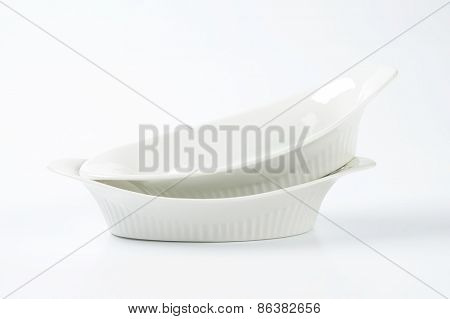 two white oval bowls on white background