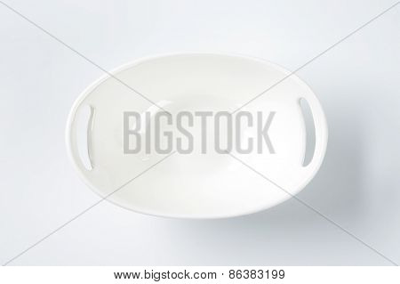 white oval bowl with handles on white background
