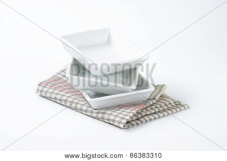 stack of white square plates on checkered dishtowel