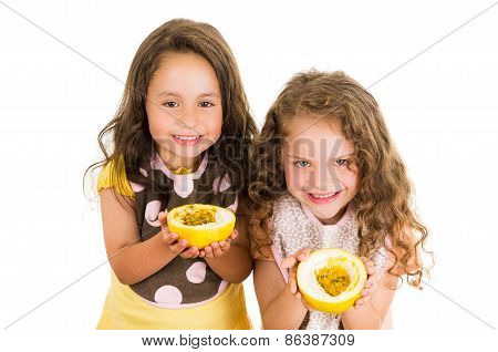 Cute little preschooler girls holding a cut open passion fruit