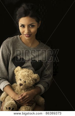 Sweet portrait of beautiful young woman holding teddy beat