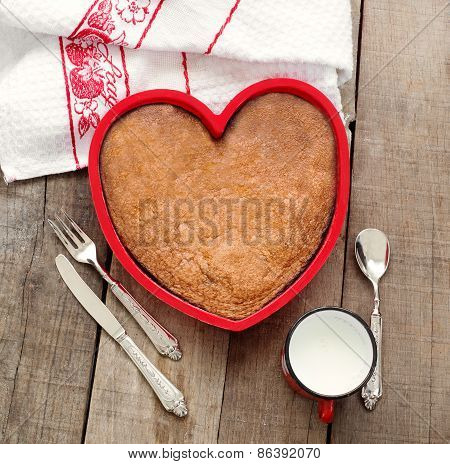 Breakfast Cake Inside Heart Baking Tin Over Wood With Vintage Silverware And Milk Mug
