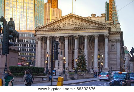 LONDON, UK - DECEMBER 19, 2014: Royal Exchange building in sun set and square with lots of office pe