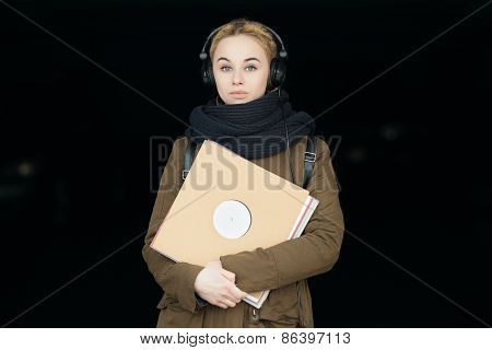 Outdoors portrait of young beautiful blonde hipster woman in big dj headphones with a vinyl records