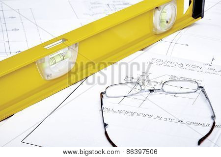 Blueprints with a Yellow Level and Reading Glasses