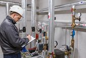 picture of hvac  - Technician inspecting heating system in boiler room - JPG