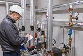 picture of boiler  - Technician inspecting heating system in boiler room - JPG