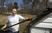 image of shingles  - Man wearing work gloves taking shingles off roof - JPG