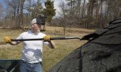 pic of shingles  - Man taking shingles off a shed roof - JPG