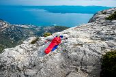 image of sleeping bag  - Young woman lying in red sleeping bag on the rocky mountain - JPG