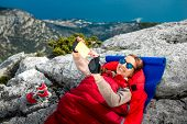 stock photo of sleeping bag  - Young woman taking selfie photo in red sleeping bag on the rocky mountain - JPG
