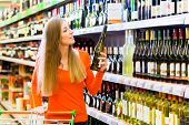 image of supermarket  - Woman buying wine in supermarket store - JPG