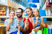 image of mall  - Family eating ice cream in shopping mall with bags - JPG