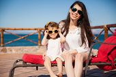picture of sunny beach  - Portrait of a cool young mom and her little girl wearing sunglasses and relaxing on the beach on a sunny day - JPG
