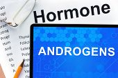 foto of hormones  - Papers with hormones list and tablet  with word androgens  - JPG