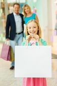 picture of mall  - Cheerful family shopping in shopping mall while little girl showing her shopping bags and smiling - JPG