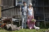 stock photo of stiff  - Couple in a stiff old classic retro pose standing in front of wooden stable while some hens grazing in the grass - JPG