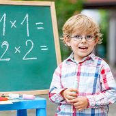 Cute Little Kid Boy With Glasses At Blackboard Practicing Mathematics poster