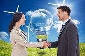 pic of turbines  - Future partners shaking hands against light bulb showing solar panels and turbines in a field with wind turbines - JPG