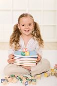 Little Girl With Books And Alphabet Wooden Blocks