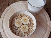 image of porridge  - oat porridge with bananas and yogurt on a wooden table