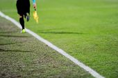 stock photo of offside  - Assistant referees running along the sideline during a soccer match - JPG
