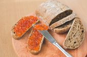 Постер, плакат: Red caviar toasts sandwich with silver knife bowl of tasty red caviar with spoon and fresh baked ho