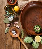 image of artichoke hearts  - Fresh artichokes prepared for baking with olive oil on wooden table top view - JPG