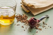 picture of tobacco-pipe  - Tobacco pipe on rustic warn green wood surface with spilled natural tobacco and a glass of whisky on the rocks - JPG