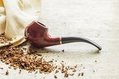 pic of tobacco leaf  - Tobacco pipe on rustic warn wood surface with spilled natural tobacco - JPG