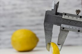 foto of vernier-caliper  - Measuring a Lemon Slice with the use of a Vernier Caliper - JPG