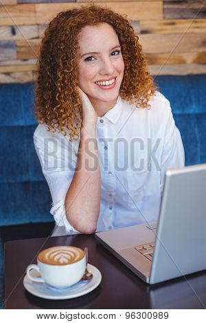Pretty ginger having coffee using laptop at the cafe
