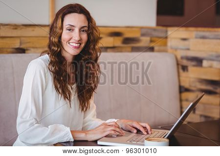 Pretty brunette having coffee using laptop at the cafe
