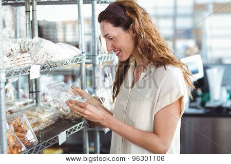 Pretty woman shopping in the bakery side view