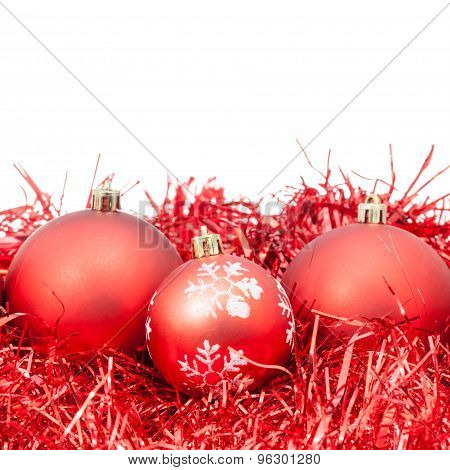 Three Red Christmas Baubles And Tinsel Isolated