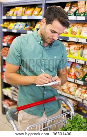 Serious man writing on list on his notepad at supermarket
