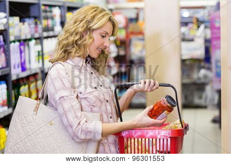 Side view of a smiling pretty blonde woman looking at a product in supermarket
