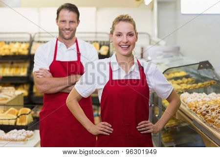 Portrait of two bakers with hands on hips in bakery
