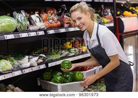 Portrait of a smiling blonde worker taking a vegetables in supermarket