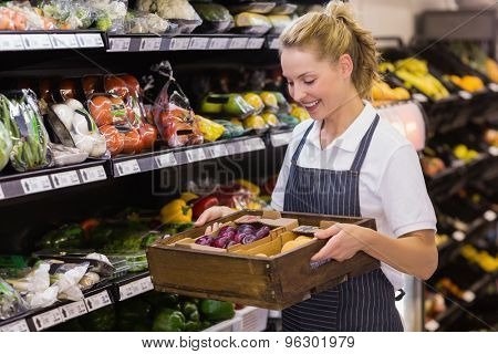 Smiling blonde worker holding a box with vegetables in supermarket
