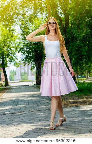 Portrait of a beautiful elegant woman in light summer clothes walking in the summer park. Beauty, fashion.
