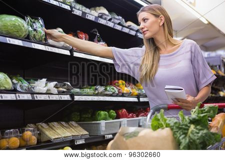 Smiling woman reading on his notepad in aisle at supermarket