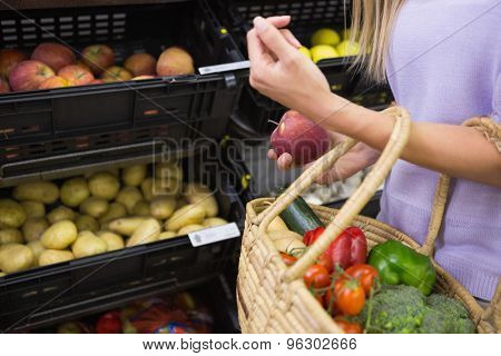 Smiling woman taking a fruits in the aisle at the supermarket