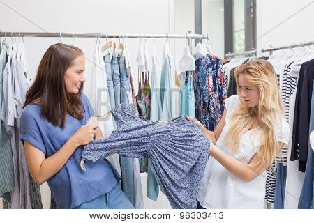 Friends fighting each other for a dress in the clothing store