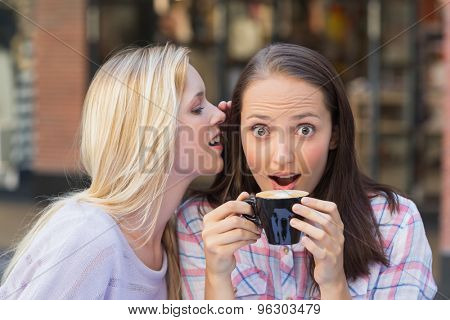 Blonde woman telling secret to her friend while drinking coffee outside at a cafe