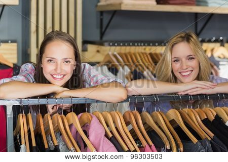 Two beautiful women with head on hand smiling at camera in clothes store