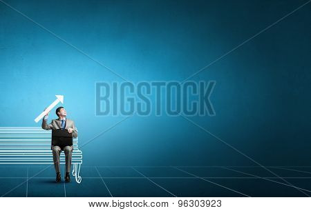 Young smiling businessman sitting on bench with briefcase in hands