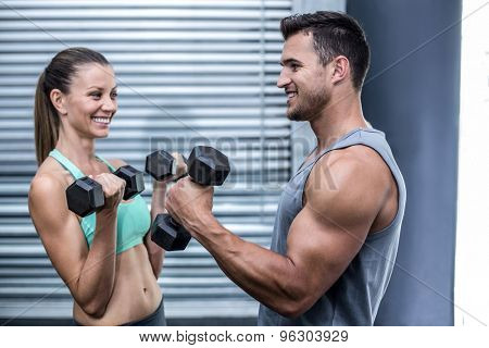 Muscular couple lifting dumbbells while facing each other