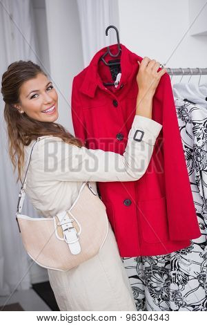 Portrait of smiling woman showing red coat and looking at camera at a boutique