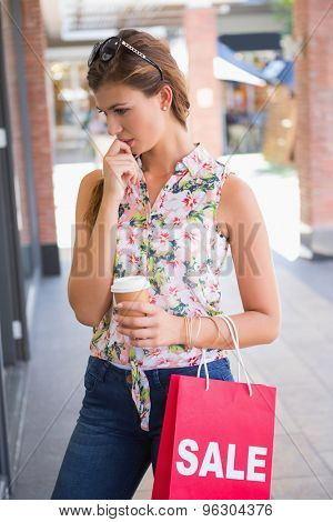 Focused woman with sunglasses, coffee to go and shopping bag at the shopping mall